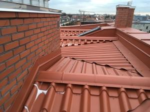 Na dachu o nachyleniu poniżej 5 stopni w oddali widać zbudowane z płyt OSB i docieplone wyjście na dach. Wyłaz na dachu płaskim