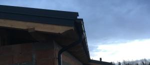 Detal wykonania szczytu budynku. Widać więźbę wykonaną na obrabiarce CNC i metalowe rynny. Ozdobna więźba z drewna klejonego warstwowo.