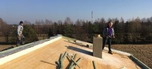 Warstwy docieplenia dachu widoczne z lewej. Na więźbie jest zamontowana nadbitka, płyta PIR, membrana, łaty i blachodachówka